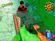 Mario confronting the Monty Mole inside a cannon on top of the cork plugging up the waterfall.